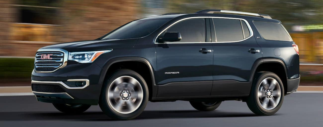 A black 2019 GMC Acadia driving on a city street