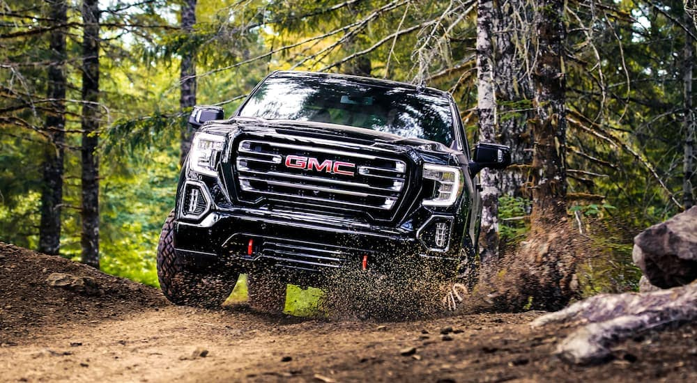 A black 2019 GMC Sierra kicks up mud on a trail
