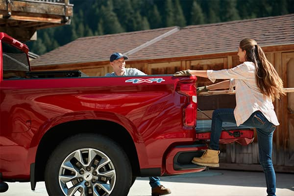 Girl stepping into red 2019 Silverado truck bed