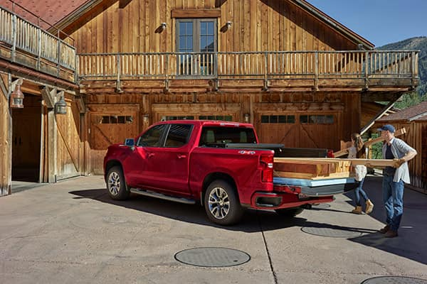 Loading wood from a red 2019 Silverado