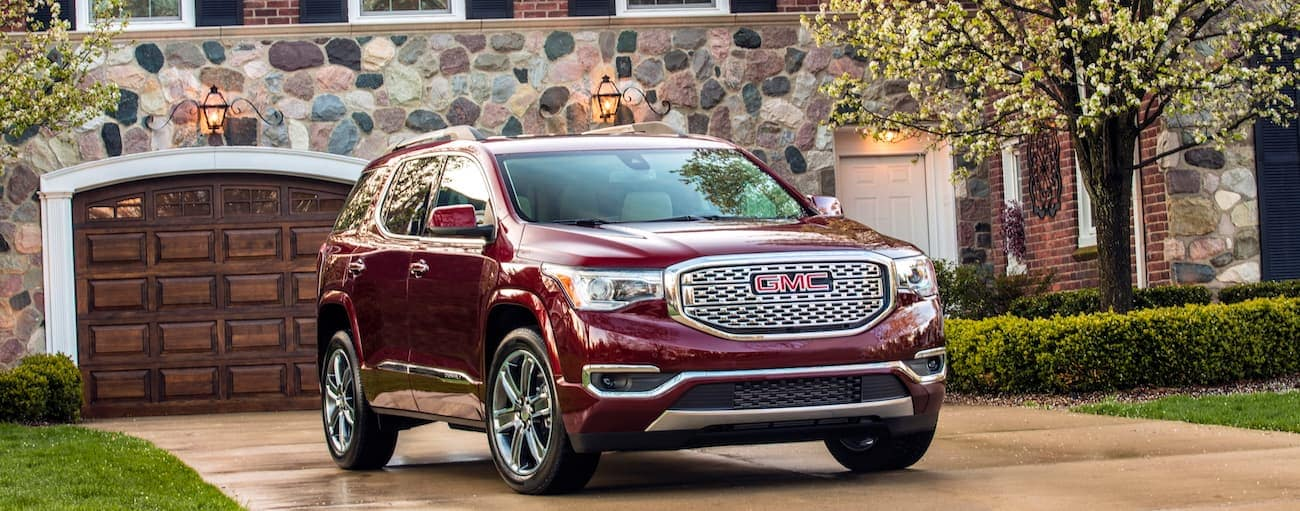 A red 2019 GMC Acadia Denali in front of a stone house