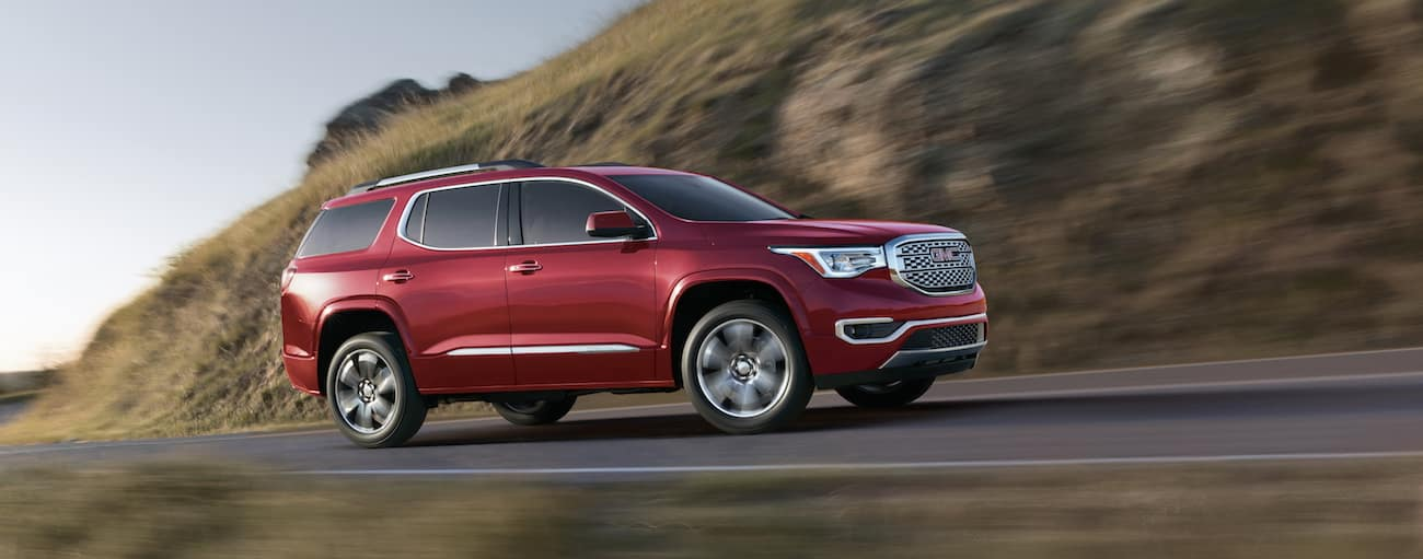 A red 2019 GMC Acadia Denali drives along a cliff-side road