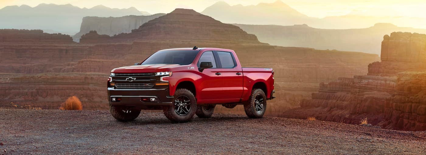 A red 2019 Chevy Silverado stands majestically in front of a mountain range at sunset