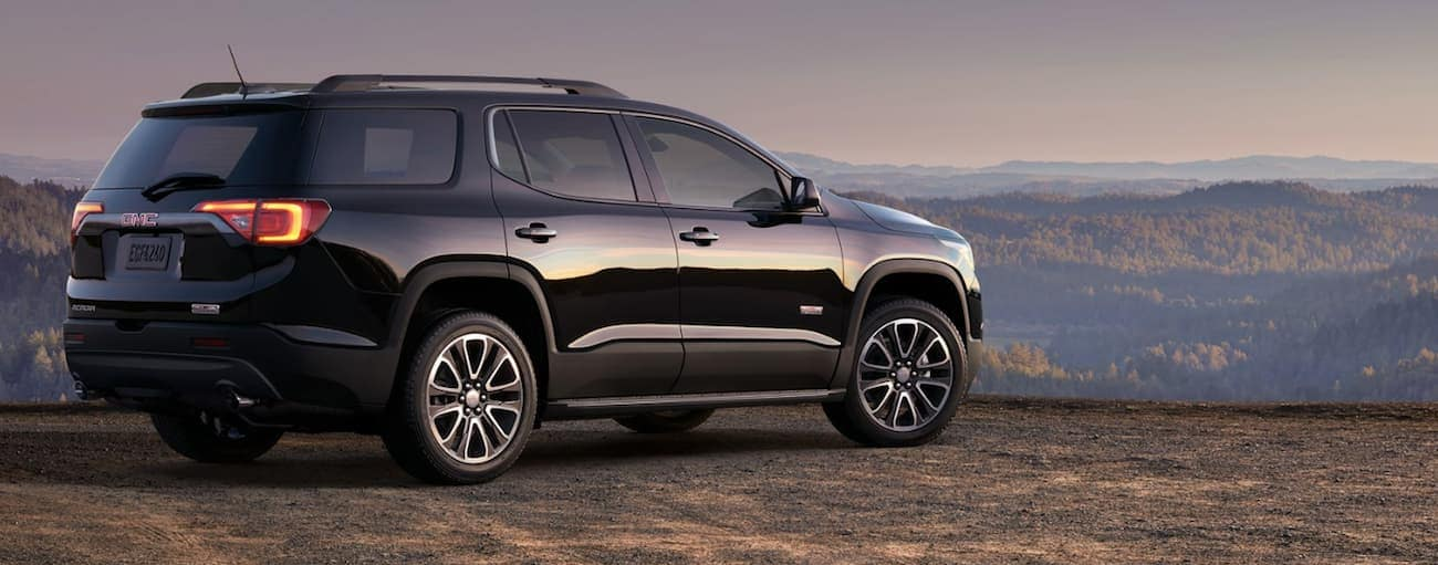 A black 2019 GMC Acadia overlooks a mountain range