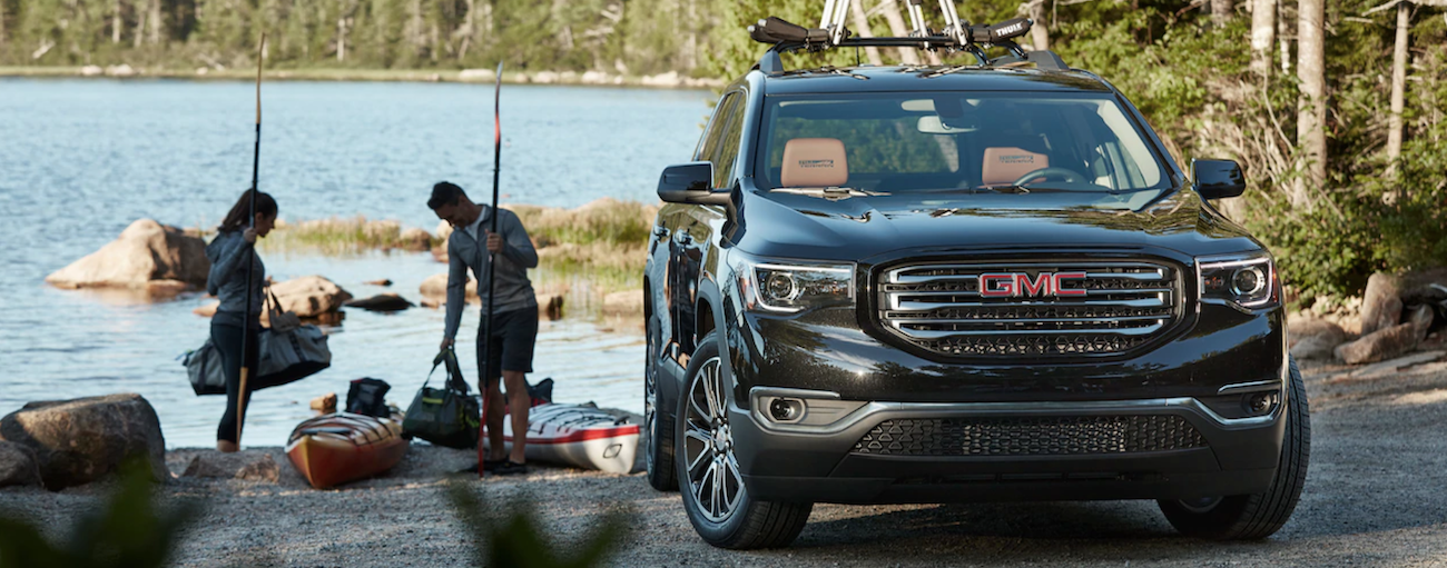 A couple next to a black 2019 GMC Acadia with kayaks