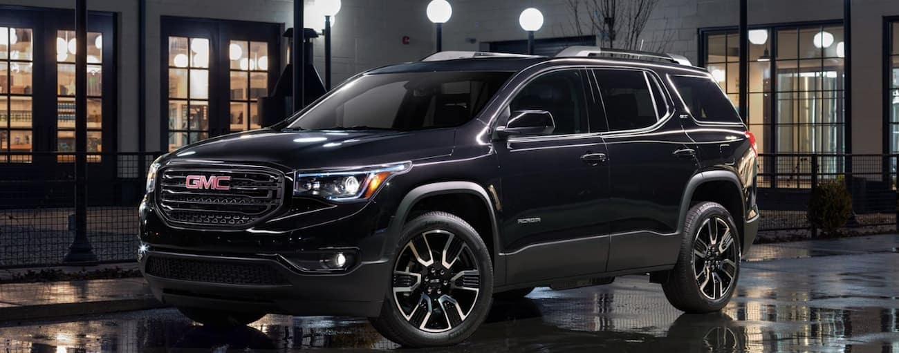 A black 2019 GMC Acadia in front of a lit up building at night