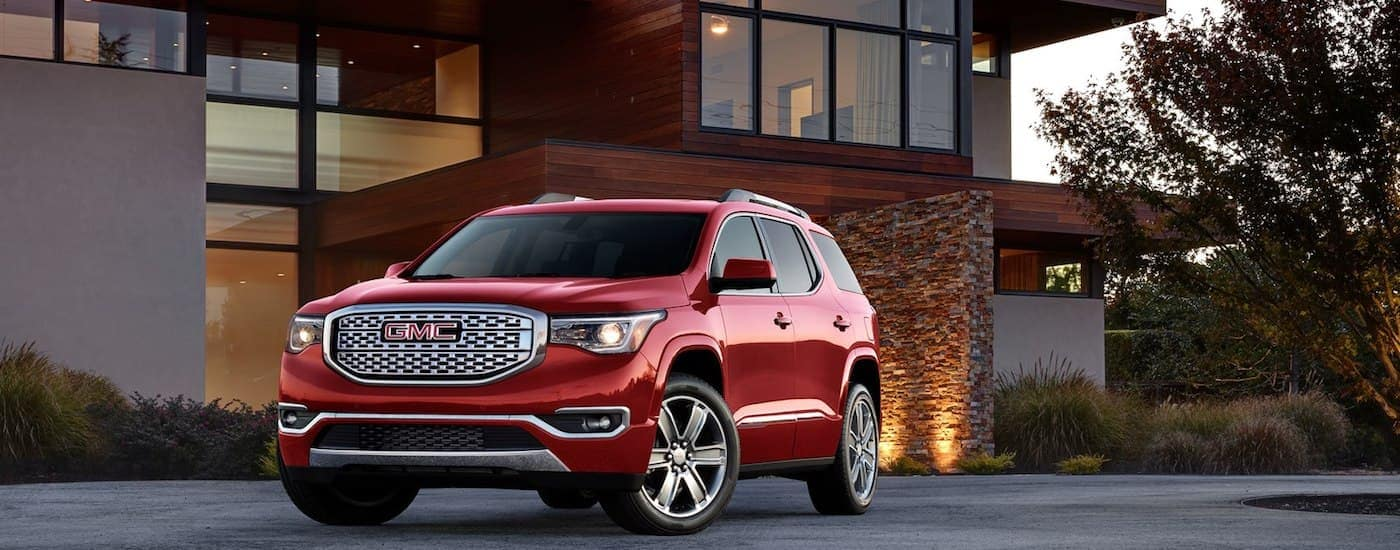 A red 2019 GMC Acadia in front of a luxury Orlando home