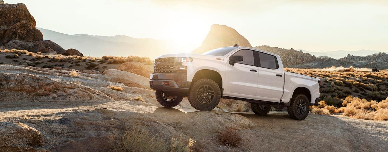 A white 2019 Chevy Silverado climbs over the competition of 2019 Chevy Silverado vs 2019 Ford F-150, also climbing rocks in a desert at sunset
