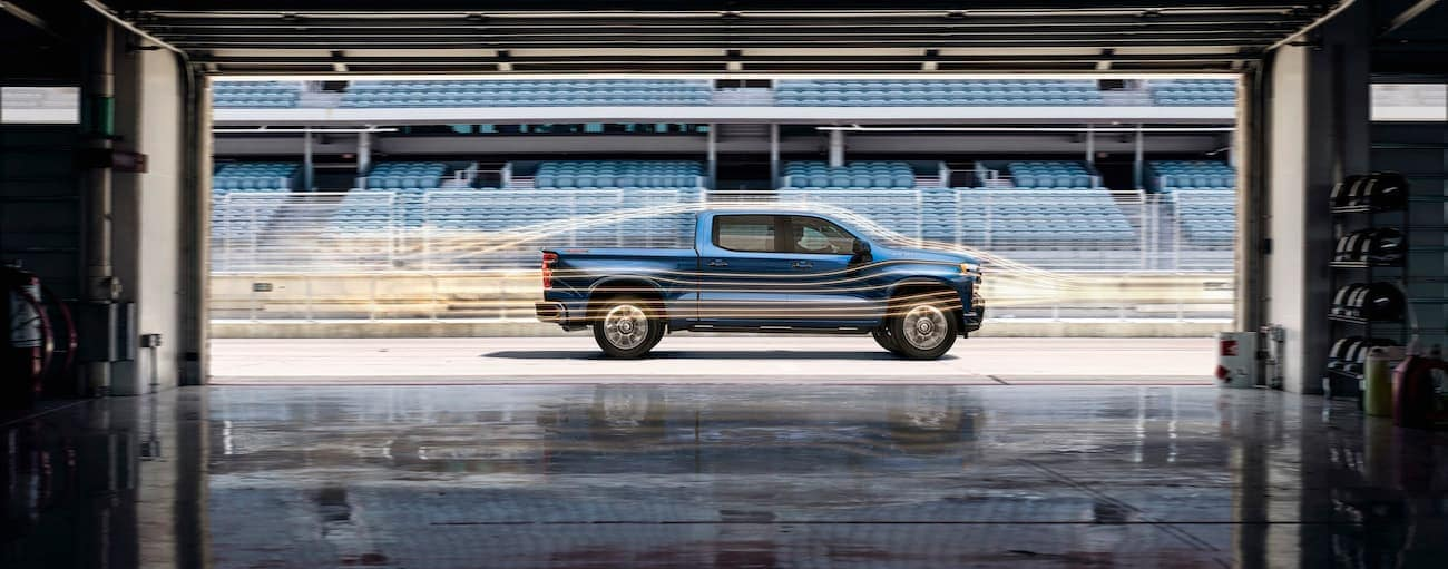 A blue 2019 Chevy Silverado on a race track with wind lines around it