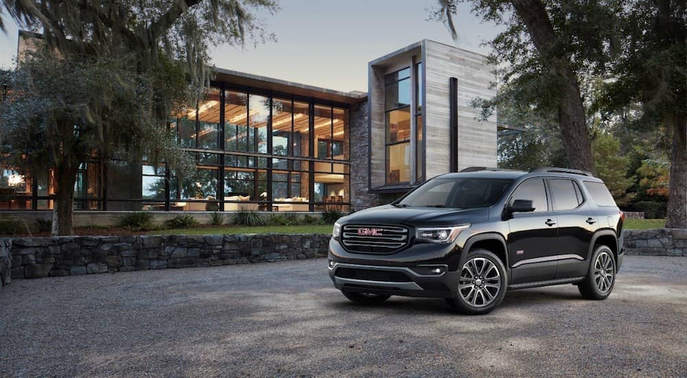 A black 2019 GMC Acadia All Terrain in front of a modern mansion