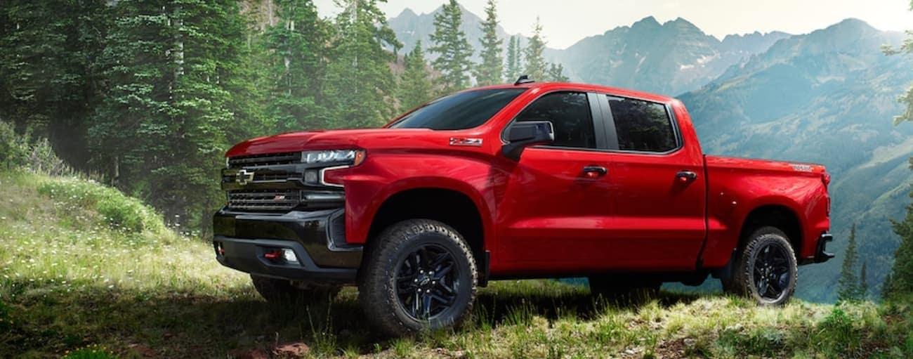A red 2019 Chevy Silverado navigating a high mountain trail