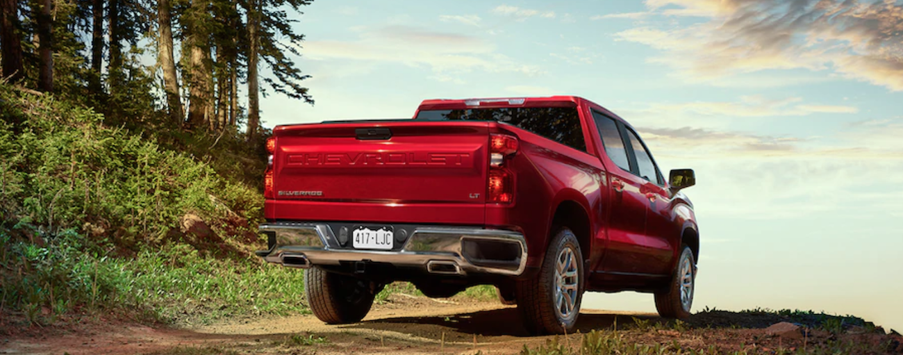 A red 2019 Chevy Silverado travels a mountain trail