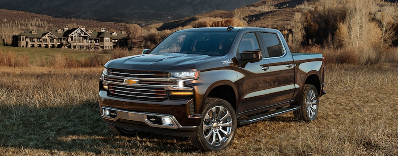 A black 2019 Chevy Silverado in a large dry field