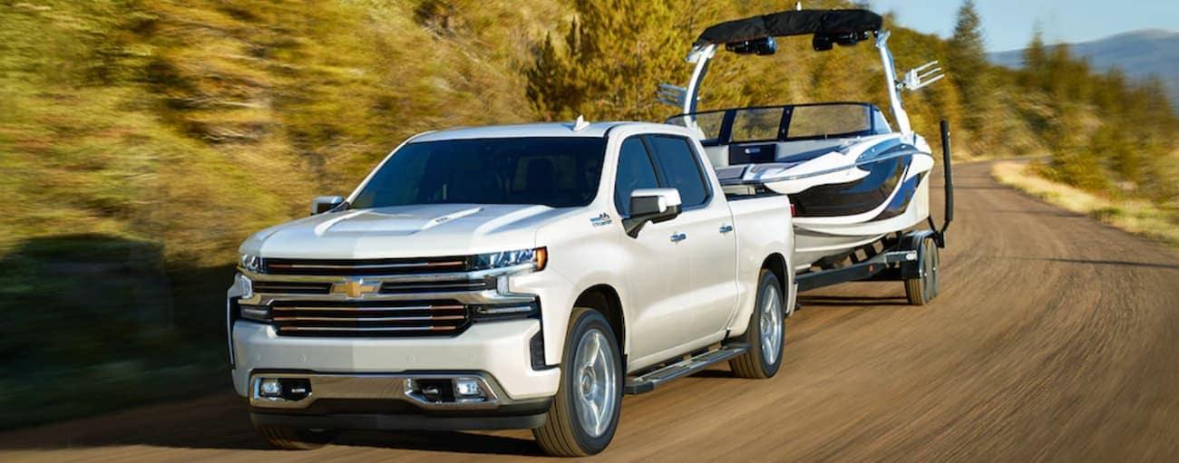 A white 2019 Chevy Silverado tows a boat up a mountain road