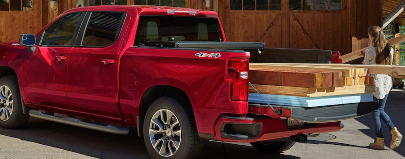 A red 2019 Chevy Silverado with a bed full of lumber