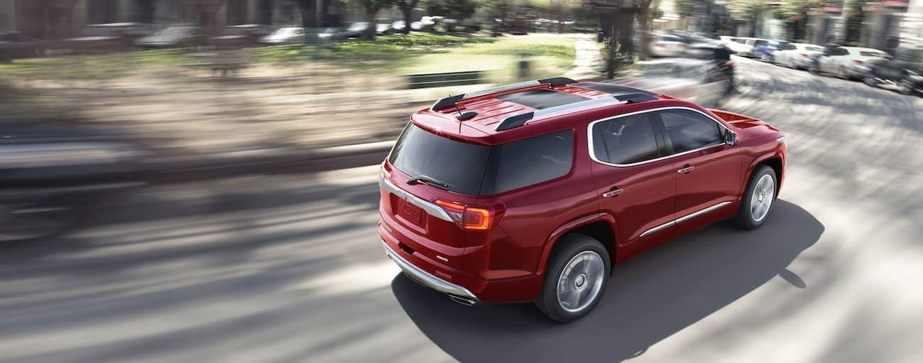 A red 2019 GMC Acadia drives a quite suburban street