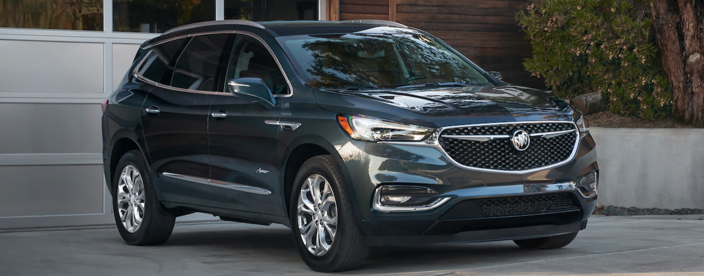 A dark sage 2019 Buick Enclave Avenir is parked in front of a garage door.