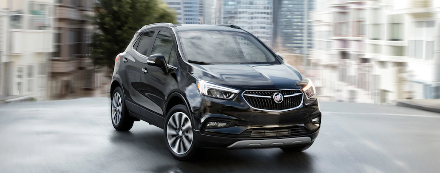 A black 2019 Buick Encore is shown on a city side street with a blurred background.