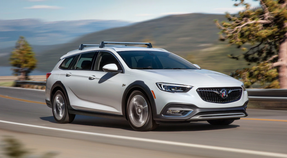 A 2019 Buick Regal TourX is driving fast along a high road. It is one of the new Buick SUVs.