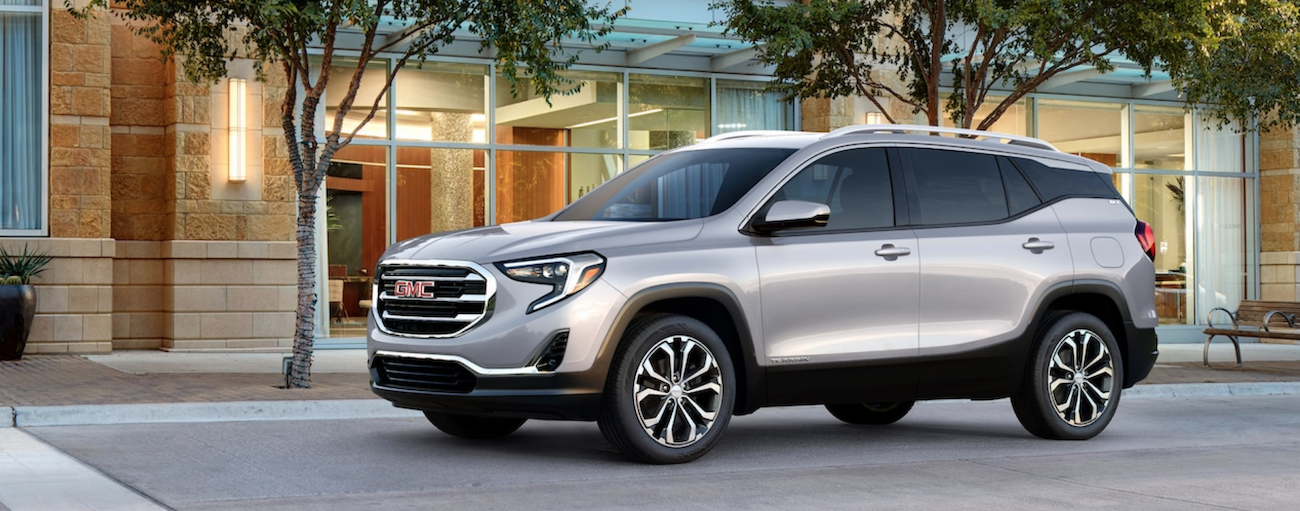 A silver 2019 GMC Terrain is parked on a city street.