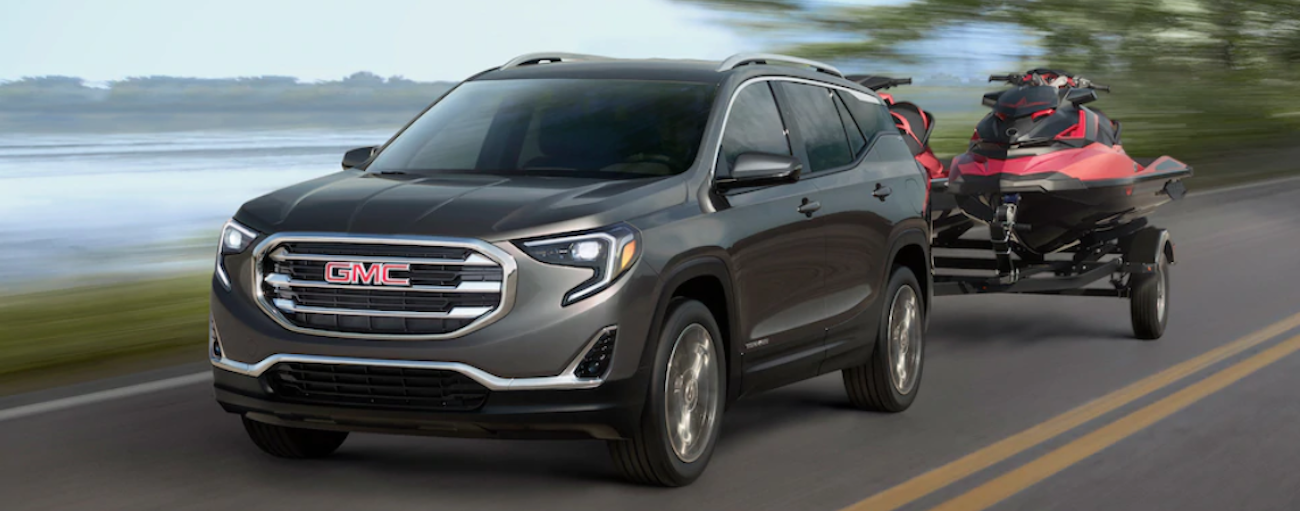 A dark Grey 2019 GMC Terrain is towing two red jet skis.