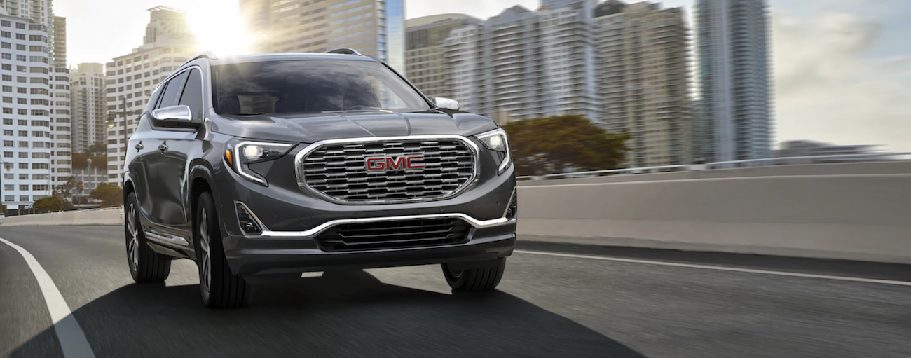 A 2019 GMC Terrain is shown driving out of a city with the sun flaring through the buildings.