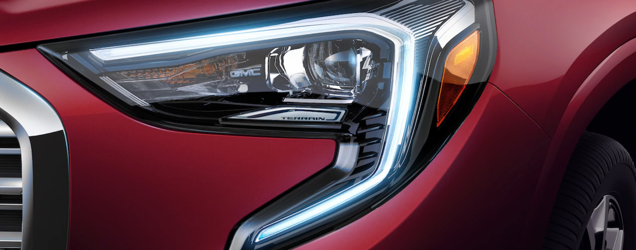 A red 2019 GMC Terrain's headlight is featured, showing the style when comparing the 2019 GMC Terrain vs 2019 Jeep Cherokee.