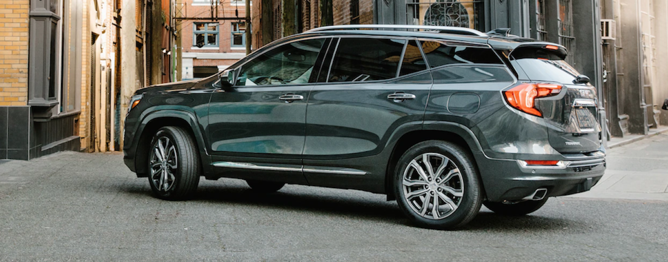 A sage 2019 GMC Terrain is taking a corner on a city side street