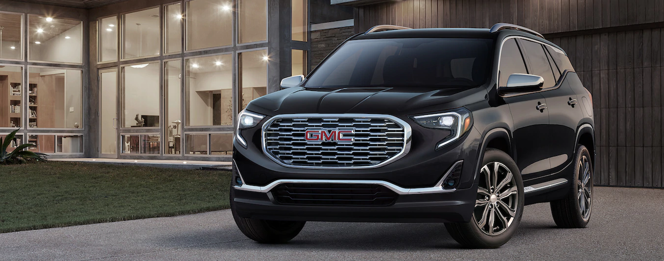 A black 2019 GMC Terrain is parked outside a modern house.