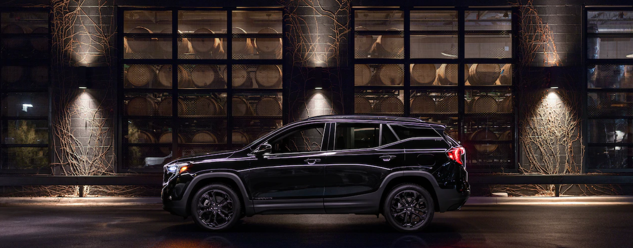 The special edition 2019 GMC Terrain Black Edition is shown at night in front of a distillery.