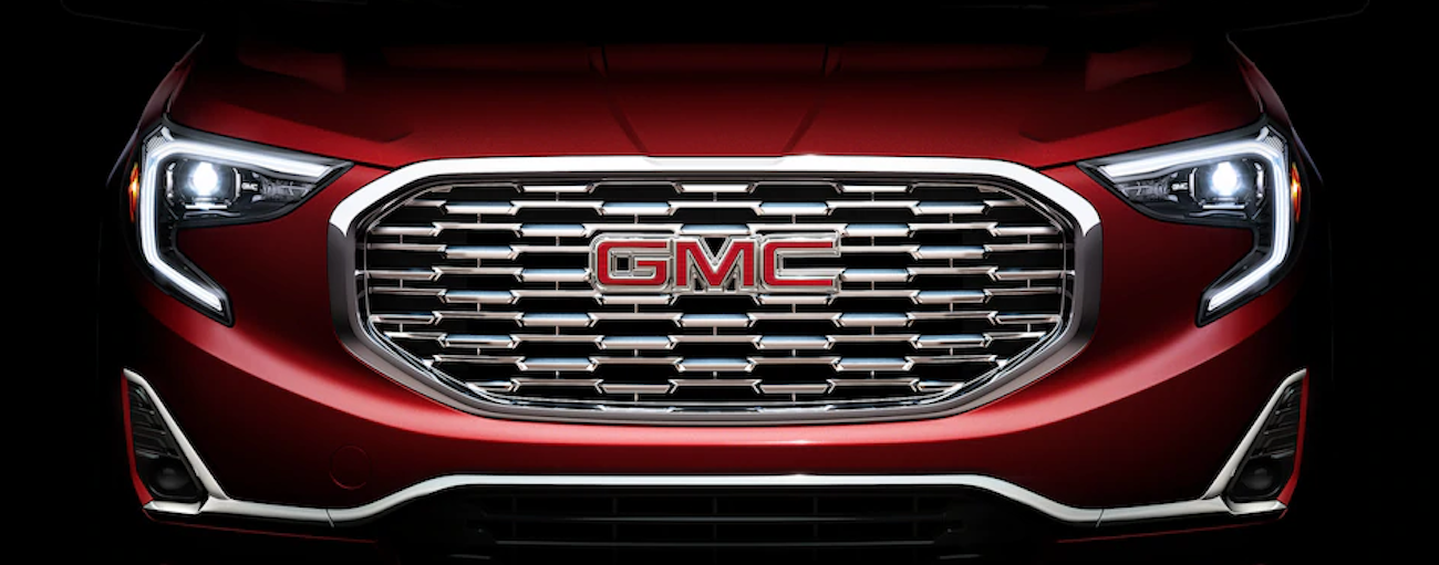 This image features the front zoomed in view of a red 2019 GMC Terrain Denali, showcasing the exterior styling when comparing the 2019 GMC Terrain vs the 2019 Honda CR-V.