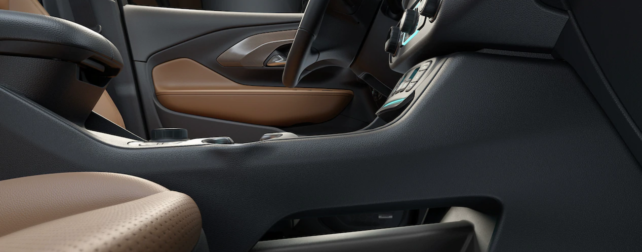 The black and tan interior of the 2019 GMC Terrain is shown from a low angle in the passenger seat.