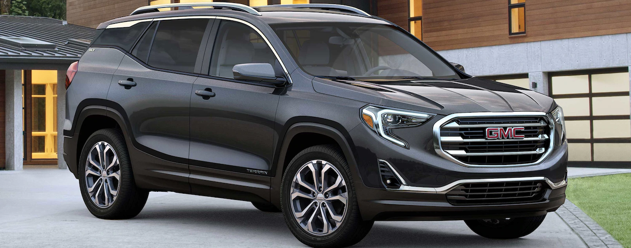 A dark grey 2019 GMC Terrain is parked outside of a modern house.