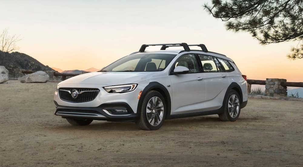A white 2019 Buick Regal Tourx is parked on sand at sunset.