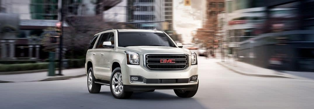 front view of white 2019 GMC Yukon driving through city streets