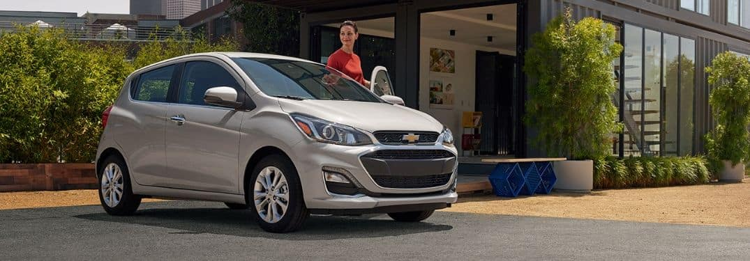 woman getting in driver's seat of silver 2019 Chevrolet Spark
