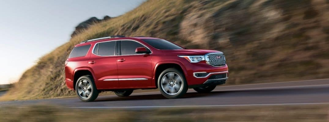 Red 2019 GMC Acadia driving on mountain
