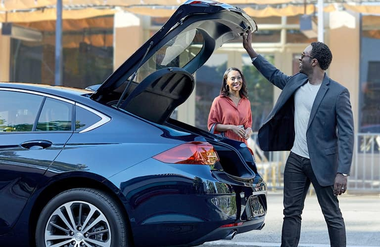 Man opening trunk of 2019 Buick Regal Sportback