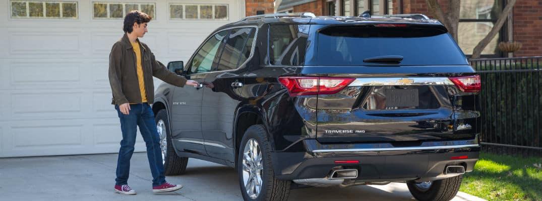 Male teenager opening door of Chevrolet Traverse
