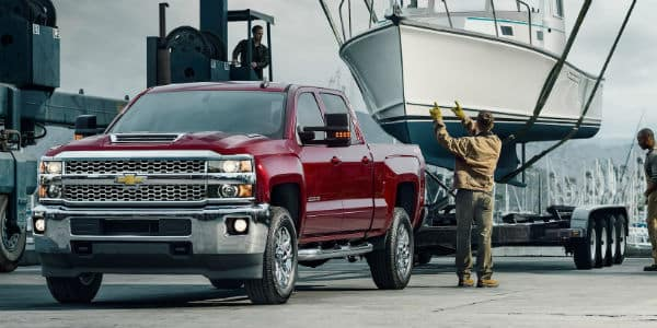 Red 2019 Chevrolet Commercial truck with boat on trailer