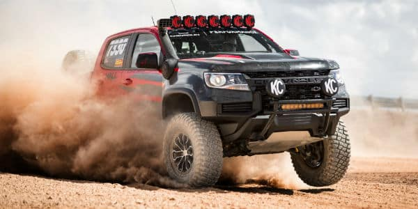 Black and red 2021 Chevrolet Colorado driving through dirt