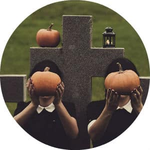 Circle image of young girls in cemetery with pumpkins