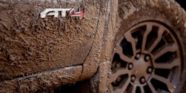 Closeup of badging on muddy 2020 GMC Sierra 1500 AT4