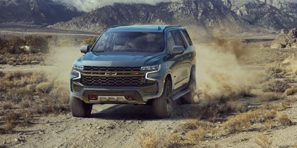 Grey 2021 Chevrolet Tahoe driving through dirt