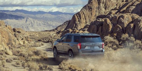 Rear view of 2021 Chevrolet Tahoe driving in desert