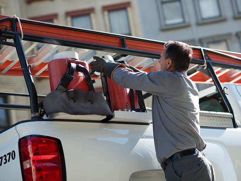 Guy putting a ladder on a Silverado Work Truck