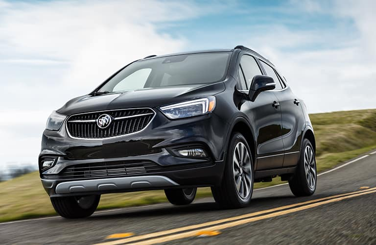 Black 2019 Buick Encore drives along a highway on a bright sunny day.