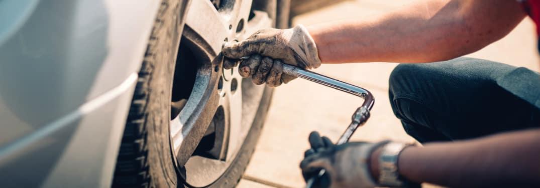 A mechanic unscrews a hubcap, presumably for tire rotation.
