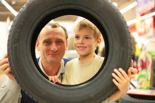 A man and child hold a tire and stare happily through its center hole.