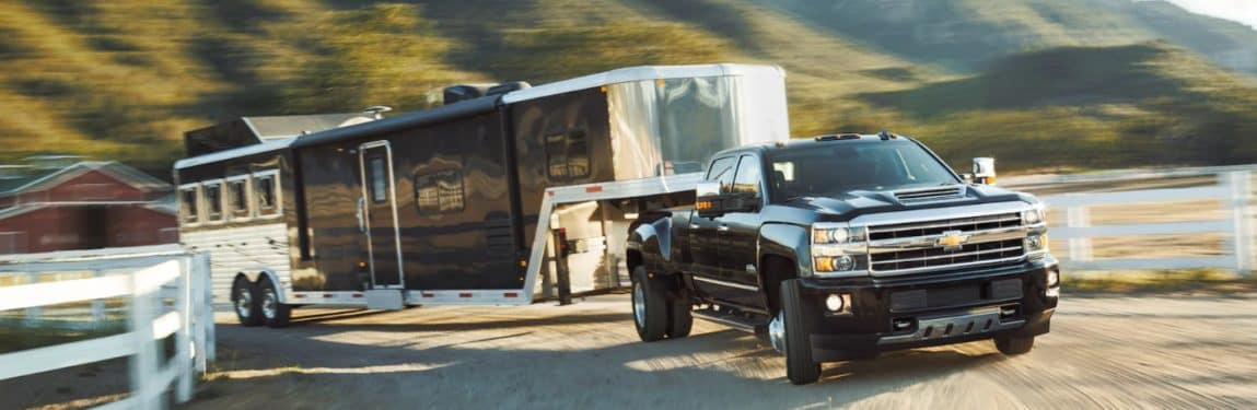 2019 Chevy Silverado HD pulls a very large trailer up a curving highway.